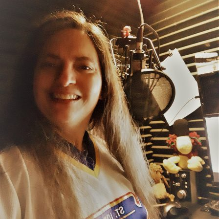 Smiling image of Lisa in her booth wearing a St. Louis Blues hockey jersey. There is a microphone with a pop filter and computer screen in the background. A stuffed Woodstock is sitting on an audio interface and papers are clipped to the foam on the walls.